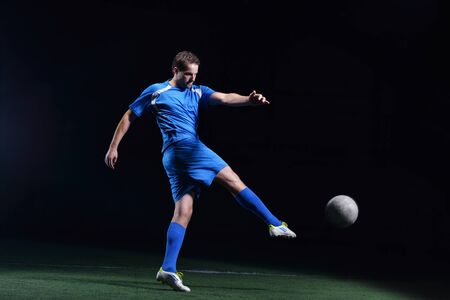 soccer player doing kick with ball on football stadium  field  isolated on black background Stock Photo - 17367099