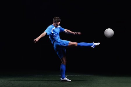 soccer player doing kick with ball on football stadium  field  isolated on black background Stock Photo - 17367087