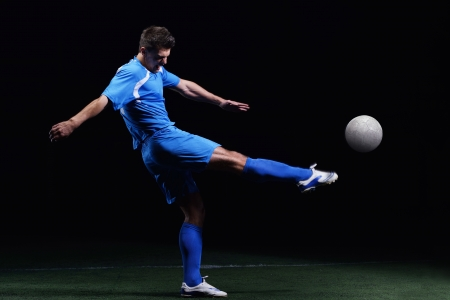 young boy feet: soccer player doing kick with ball on football stadium  field  isolated on black background