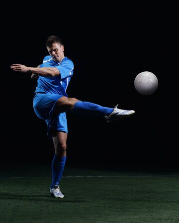 soccer player doing kick with ball on football stadium  field  isolated on black background Stock Photo - 17367140