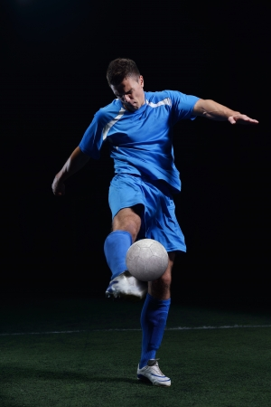 soccer player doing kick with ball on football stadium  field  isolated on black background Stock Photo - 17368398
