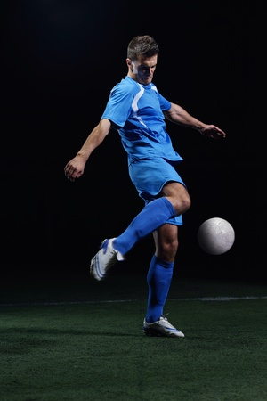 soccer player doing kick with ball on football stadium  field  isolated on black background Stock Photo - 16715124