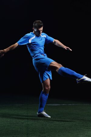 soccer player doing kick with ball on football stadium  field  isolated on black background Stock Photo - 16715123