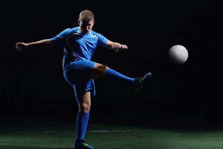 soccer player doing kick with ball on football stadium  field  isolated on black background Stock Photo - 16523022