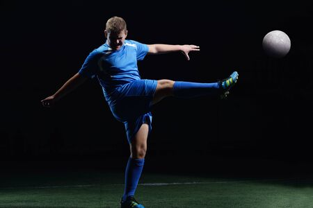 soccer player doing kick with ball on football stadium  field  isolated on black background Stock Photo - 16523089