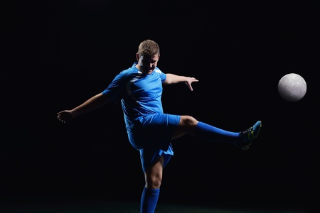 soccer player doing kick with ball on football stadium  field  isolated on black background Stock Photo - 16523114