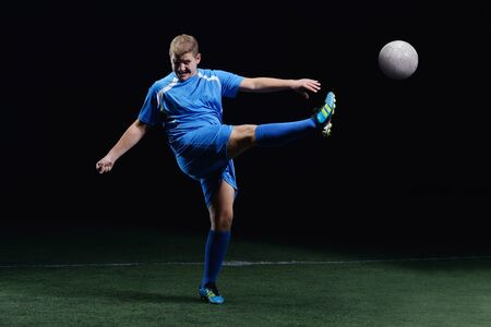 soccer player doing kick with ball on football stadium  field  isolated on black background Stock Photo - 16522964