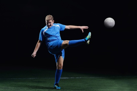 soccer player doing kick with ball on football stadium  field  isolated on black background Stock Photo - 16523117