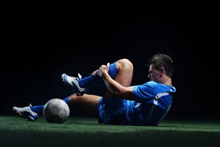 soccer player doing kick with ball on football stadium  field  isolated on black background photo