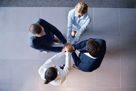business people group joining hands and representing concept of friendship and teamwork,  low angle view Stock Photo - 16581617