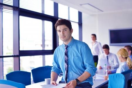 Portrait of a handsome young  business man  on a meeting in offce with colleagues in background Stock Photo - 16581445