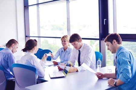 CONFERENCE TABLE: Group of happy young  business people in a meeting at office Stock Photo