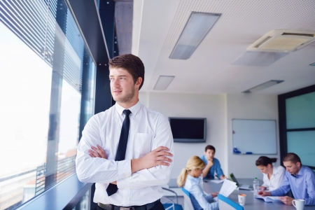 Portrait of a handsome young  business man  on a meeting in offce with colleagues in background Stock Photo - 16580856