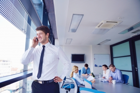 Portrait of a handsome young  business man  on a meeting in offce with colleagues in background Stock Photo - 16581458