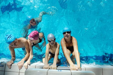 kids swimming pool: happy children kids group  at swimming pool class  learning to swim