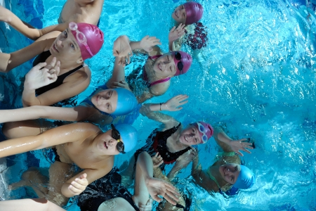 swimming cap: happy children kids group  at swimming pool class  learning to swim