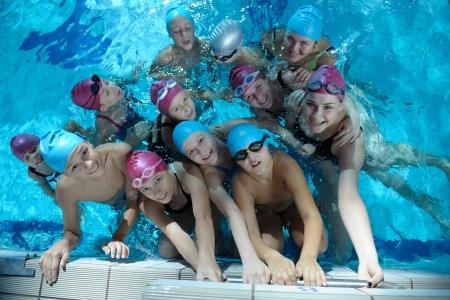 niños nadando: feliz grupo de niños hijos en clases de natación de la piscina para aprender a nadar