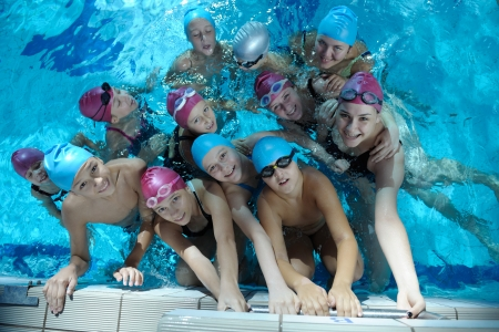swimmer: happy children kids group  at swimming pool class  learning to swim