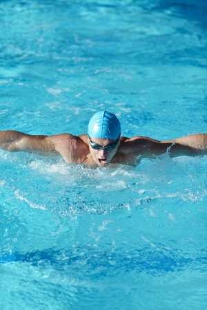 swimmers: Happy muscular swimmer wearing glasses and cap at swimming pool and represent health and fit concept Stock Photo