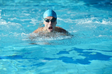 Musculoso nadador feliz con gafas y gorro de piscina y representan la salud y el concepto de ajuste photo