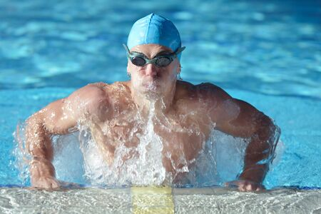 Happy muscular swimmer wearing glasses and cap at swimming pool and represent health and fit concept photo