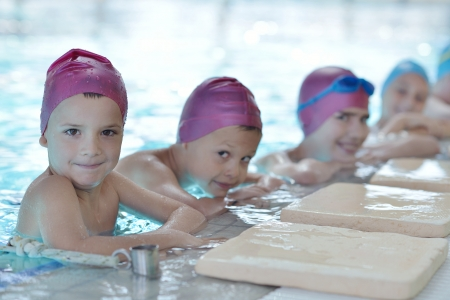 to swim: happy children kids group  at swimming pool class  learning to swim