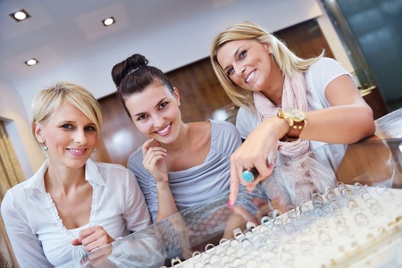 fashion jewelry: happy girls group  have fun while shopping in jewelry store Stock Photo
