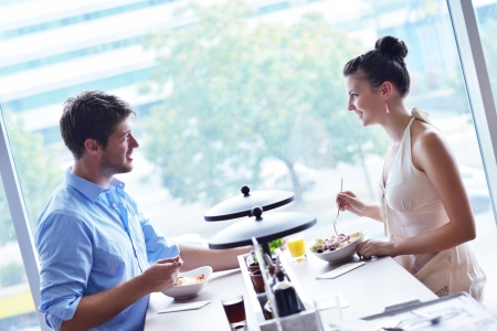 happy young couple: A young couple sitting at a table and have lunch at an outdoor restaurant
