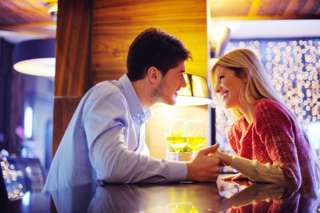 date: romantic evening date in restaurant  happy young couple with wine glass tea and cake