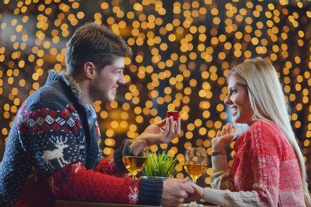 jovenes enamorados: El joven da un regalo anillo de bodas a la niña en el restaurante Foto de archivo