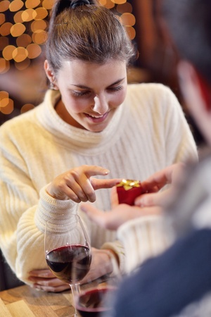 The young man gives a wedding ring   gift to  girl in restaurant photo
