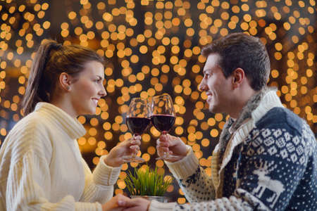 romantic evening date in restaurant  happy young couple with wine glasses photo