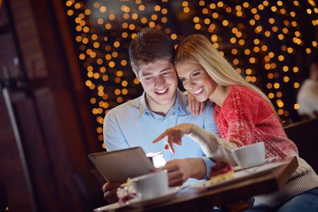 happy young couple with a tablet computer in restaurant photo