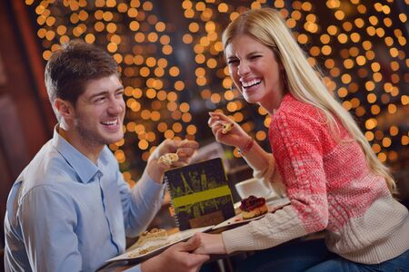 romantic evening date in restaurant  happy young couple with wine glass tea and cake photo