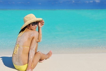 happy young pretty asian woman resting on sand at tropical beach photo
