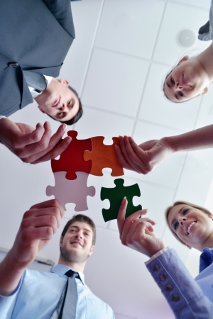 Group of business people assembling jigsaw puzzle and represent team support and help concept photo