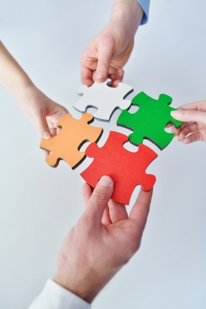 team building: Group of business people assembling jigsaw puzzle and represent team support and help concept