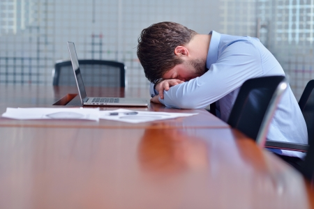 overworked: Young business man with problems and stress in the office Stock Photo
