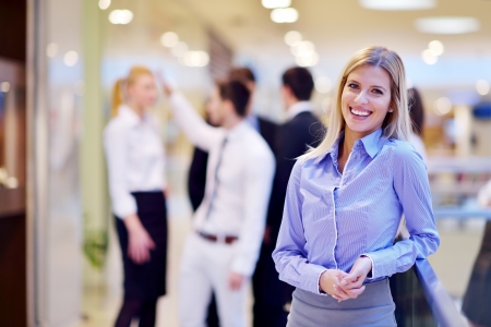 happy business team: business woman  with her staff,  people group in background at modern bright office indoors Stock Photo