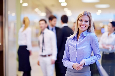 trabajo en oficina: mujer de negocios con su personal, las personas del grupo en segundo plano en las modernas oficinas en el interior brillantes Foto de archivo