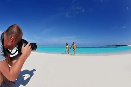 photographer taking photo of models couple on beautiful tropical beach at summer Stock Photo - 18319957