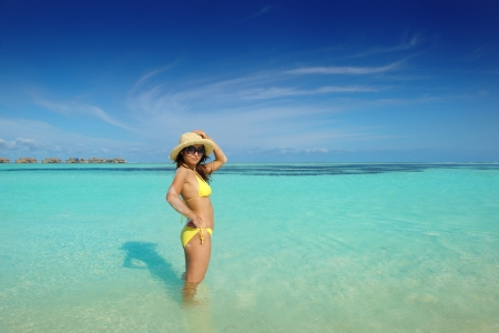 happy young beautiful asian woman resting on sand at tropical beach photo