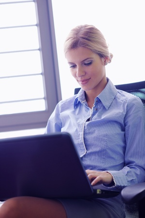 portrait of Young pretty business woman work on  notebook computer  in the bright modern office indoors Stock Photo - 18319314