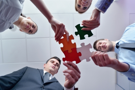 working woman: Group of business people assembling jigsaw puzzle and represent team support and help concept