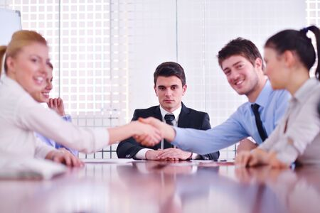 deal in: business people shaking hands make deal and sign contract in bright modern office
