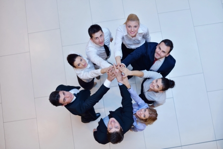 joining hands: business people group joining hands and stay as team in circle  and representing concept of friendship and teamwork