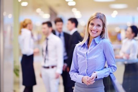 회사: 실내 현대 밝은 사무실에서 배경에서 그녀의 직원과 사업 여자, 사람들은 그룹