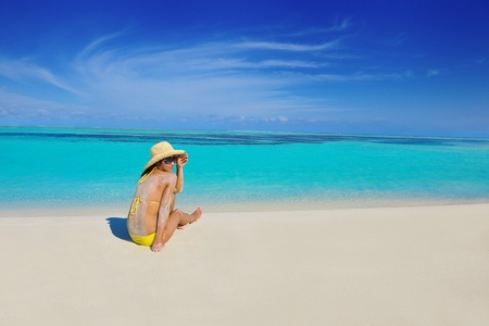 happy young beautiful asian woman relax on sand at tropical beach with cristal clear sea in background photo