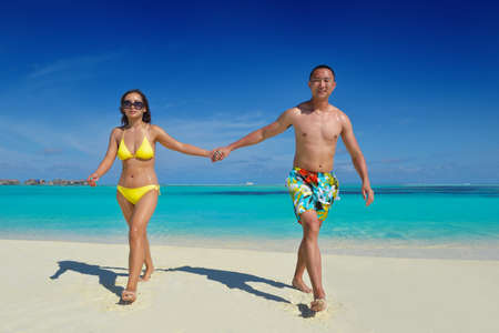 happy young asian couple have fun and romantic time at  summer on beautiful white sand beach photo