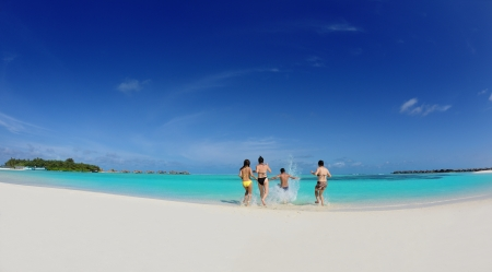 group of happy young people have fun and joy at the  white sand  beach on beautiful summer  day photo